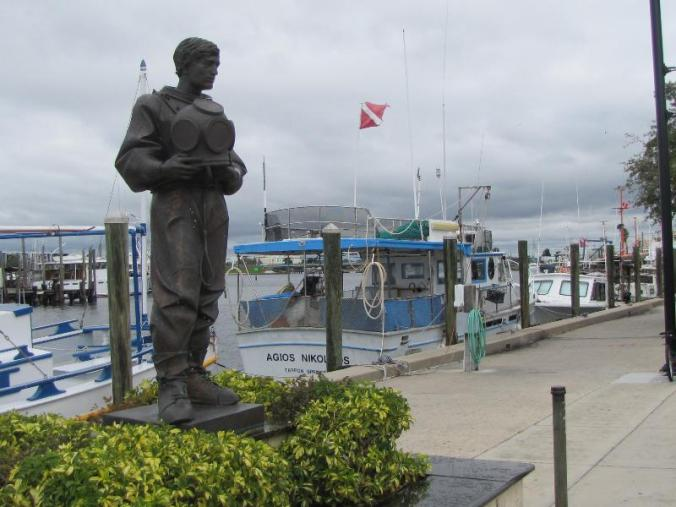 Statue honoring the Greek sponge divers. That is a real sponge boat tied to the dock.