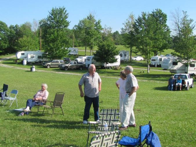 Owner Steve Garten, center, chattng wth guests: a portion of the beautiful RV sites are in the background.