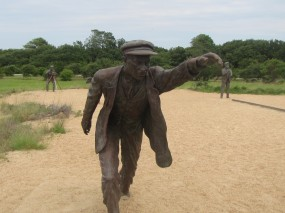 Statue of Wilbur running alongside the plane piloted by Orville